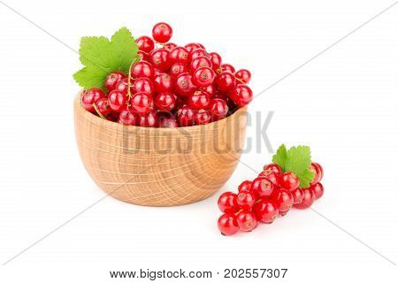 Red currant berries in a wooden bowl with leaf isolated on white background.