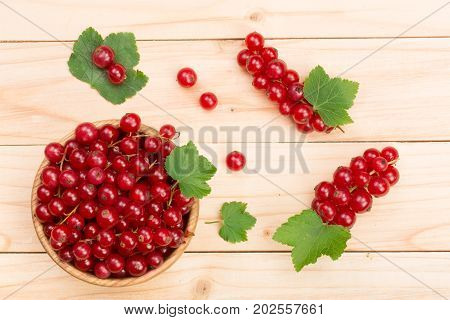 Red currant berries in a wooden bowl with leaf on the light wooden background. Top view.