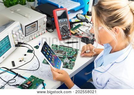 Young attractive female digital electronic engineer using tablet computer PC in the laboratory
