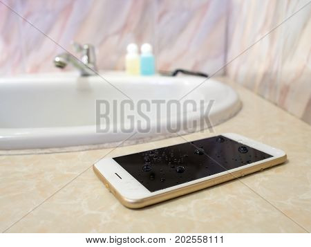 Water damage smart phone in wash basin. Water damage waterproof concept.