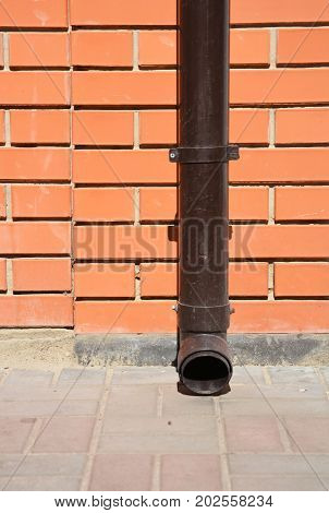 Roof Gutter Plastic Holder and Downspout Pipe without any Drainage Hole on Pavement.
