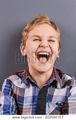 Portrait of laughing little boy. Close up studio portrait of happy joyful laughing blond hair boy. Little boy in checkered shirt laughing on grey background.