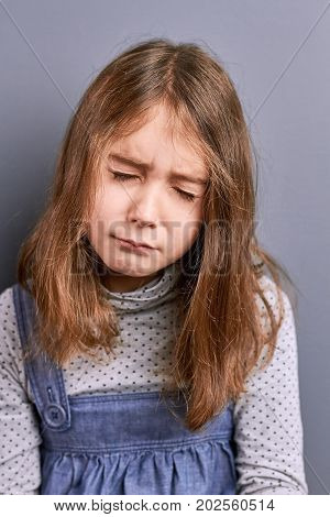 Portrait of little girl with closed eyes. Studio shot of sad tired caucasian little girl. Portrait of unhappy little girl.
