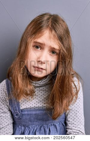 Portrait of little upset girl. Studio shot of unhappy pretty little girl, grey background. Brown hair little girl looking frustrated.