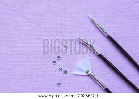Brush And Rhinestones To Nails. Lace On Black Fabric Background. Nail Art