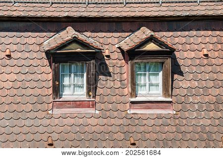 Bamberg Germany - May 22 2016: Traditional windows on the tiled roof of old half-timbered colorful house close-up in Bamberg Germany.