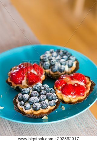 Mascarpone pies with blueberries and strawberries on a blue plate on wooden table in soft focus