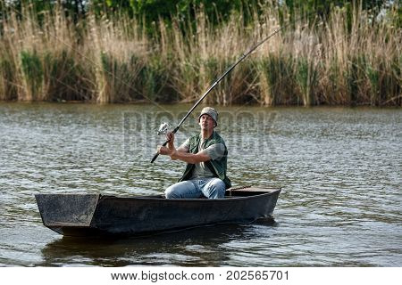 Fisherman catches a fish. fisherman with rod in hand