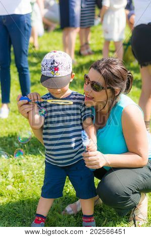 Woman and toddler boy with Mickey Mouse hat blowing soap bubbles on the Festiwal Baniek Mydlanych at a park on August 2017 in Poznan Poland