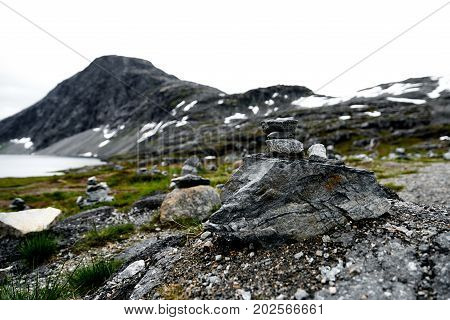 Hiking stones in focus with snow covered mountains and a lake in the unsharp background in norway