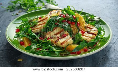 Grilled Halloumi Cheese salad with orange, rocket leaves, pomegranate and pumpkin seed. healthy food.