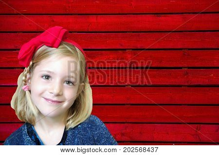Portrait of a little six years old smiling cute blond girl with a red bow on his head on red wooden wall background.