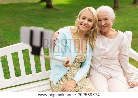 family, technology and people concept - happy smiling young daughter and senior mother sitting on park bench and taking picture with smartphone selfie stick