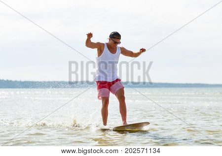 skimboarding, water sport and people concept - happy young man riding on skimboard on summer beach