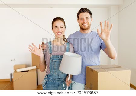 mortgage, people and real estate concept - happy couple with boxes and lamp moving to new home