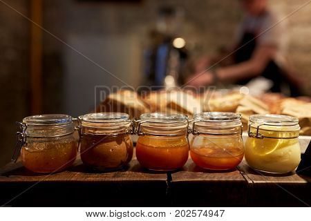food, cooking and gourmet concept - jars with craft jam or sauce at grocery store