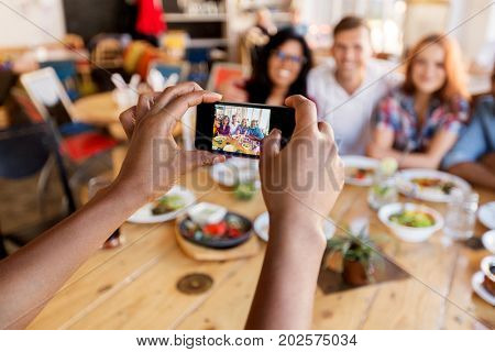 leisure, technology and people concept - group of happy international friends eating and taking picture by smartphone at restaurant table