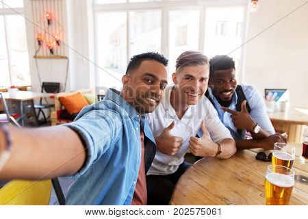 people, friendship and leisure concept - happy male friends drinking beer, taking selfie and showing thumbs up at bar or pub