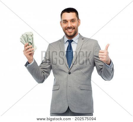 business, people and finances concept - smiling businessman with bundle of american dollar cash money showing thumbs up