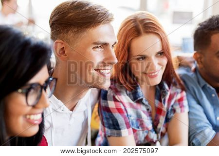 friendship and people concept - group of happy international friends at restaurant