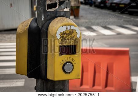 Broken traffic light button with the word nacisnij that means push by a street