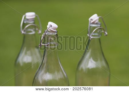 Three old-fashioned authentic Dutch milk bottles against a green natural background