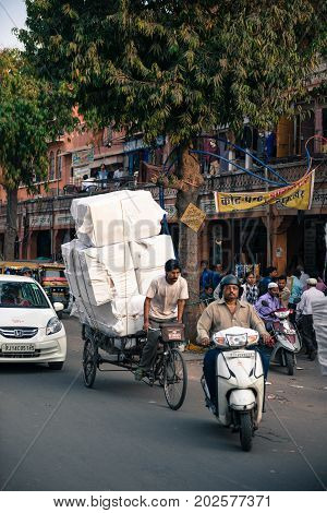 JAIPUR RAJASTHAN INDIA - MARCH 10 2016: Vertical picture of indian man working as rickshaw in Jaipur known as pink city of Rajasthan in India.