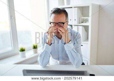 business, overwork, deadline and people concept - tired businessman in eyeglasses with laptop computer rubbing eyes at office