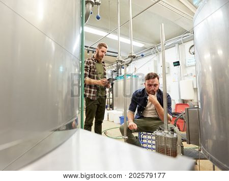 manufacture, business and people concept - men with tablet pc computer and filter craft brewery or non-alcoholic beer production plant