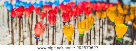 Banner Flowers Made From A Plastic Bottle. Plastic Bottle Recycled. Waste Recycling Concept Long For
