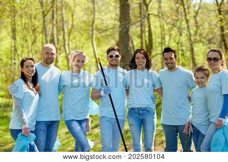 volunteering, charity, cleaning, people and ecology concept - group of happy volunteers with garbage bags and rake in park
