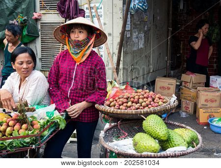 Hanoi, Vietnam - May 22, 2017: Woman Selling Tropical Fruit On A Busy Hanoi Street Fruit Market Wear