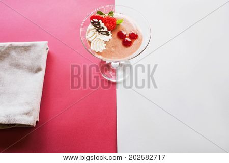 Creamy strawberry dessert on contrast crimson and white background. Sweet fruit souffle decorated with fresh red berry, chocolate and mint, free space below
