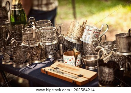 Lot of antique metal glass holders at a flea market. Many old ornate cup holders at a garage sale