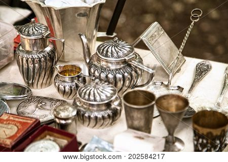 Antique silver teapots creamer and other utensils at a flea market. Old metal tableware collectibles at a garage sale