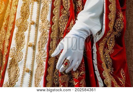 Clothes Of A Historical Imperial Woman With Red Elements, A Hand In White Gloves And A Ring With A P