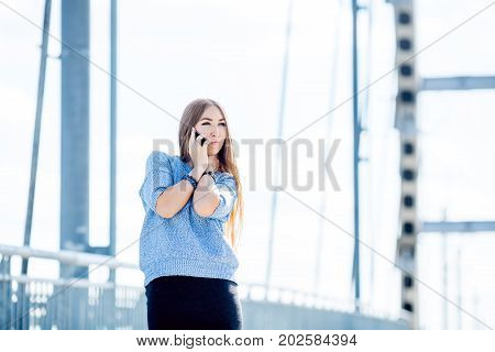 Beautiful young businesswoman using cell phone on city street