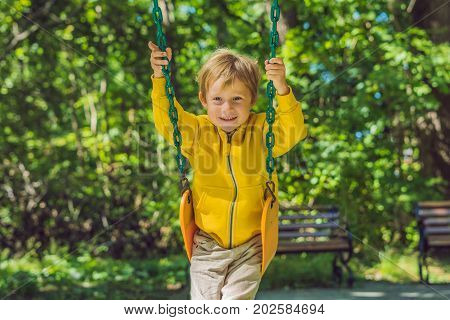 A Boy In A Yellow Sweatshirt Sits On A Swing On A Playground In Autumn