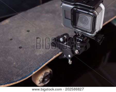 Action camera for professional video shooting of extreme sport tricks, training and competitions, fixed on skateboard rubbed deck on black background