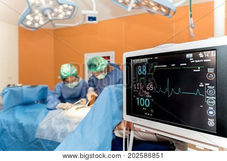 Medical monitor with doctor and an assistant in the operating room for surgical venous vascular surgery clinic.