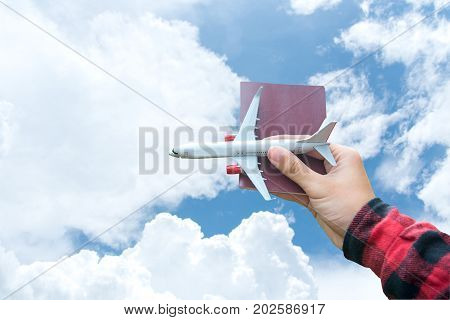Tourist holding airplane and passport flight travel traveller fly on the blue sky for travelling citizenship air on the around world. Travel Concept.