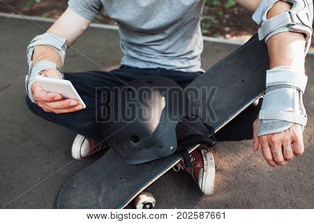 Professional skateboarder checking online network. Extreme sport challenge and competition combining with active social life, internet and mobile phones. Urban lifestyle and culture of young people