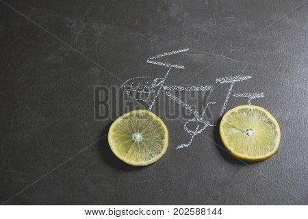 lemon slice shape wheel of bicycle paint by chalk on black table background.