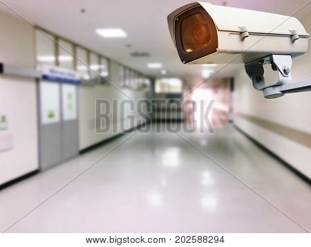CCTV security camera system operating with blurred image of hospital or clinic interior for background surveillance security and safety technology conceptCCTV security camera system operating with blurred image of hospital or clinic interior for backgroun