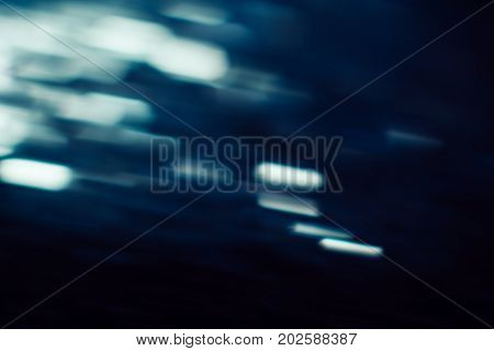 Abstract background of defocused white lights motion blur. Glowing urban backdrop, heavy night illumination city glimmers, bokeh