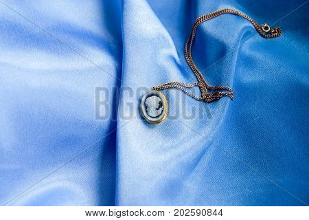 Gold Chain With A Cameo Hanging, Chiseled Female Profile On Smooth Sky-blue Silk