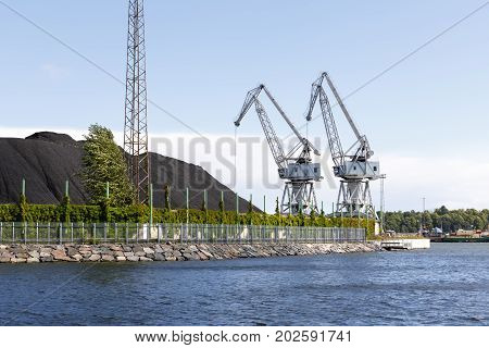 Two large white industrial cranes next to large coal piles