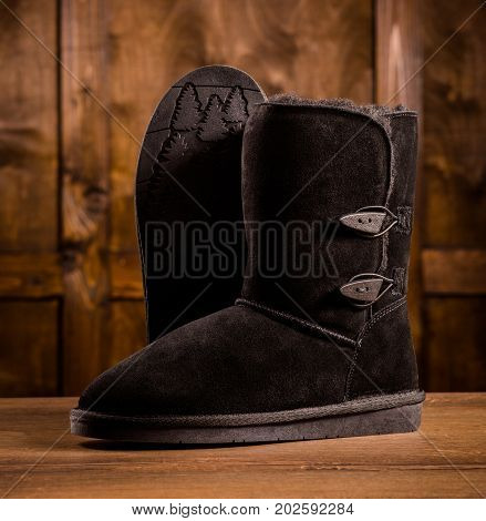 Pair of warm suede boots. Boots standing on wooden desk. One boot showing sole.