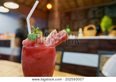 Watermelon spinning as sweet juice in glass on the table with restaurant background