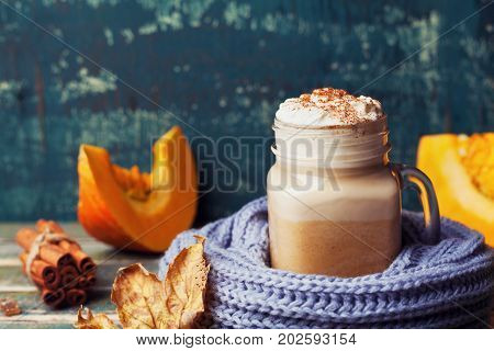 Flavored pumpkin spiced latte or coffee in cup decorated knitted scarf on teal vintage background. Autumn fall or winter hot drink. Cozy breakfast.